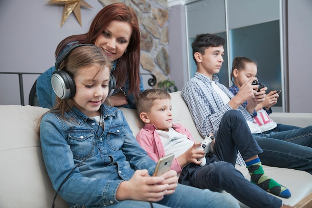 Woman looking at children playing video games Free Photo