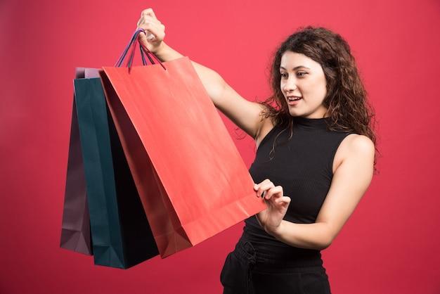 Женщина смотрит на свою новую одежду покупки на красном фоне Бесплатные Фотографии