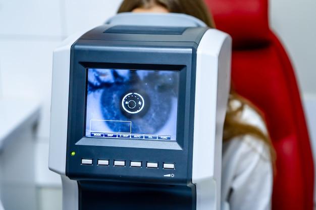 Женщина смотрит на машину для проверки зрения рефрактометра в офтальмологии Premium Фотографии