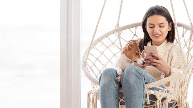 彼女の犬と一緒にスマートフォンを見ている女性 無料写真