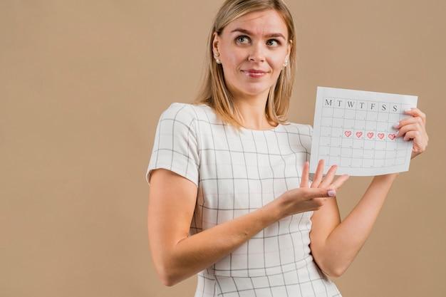 よそ見や彼女の期間カレンダーを示す女性 無料写真