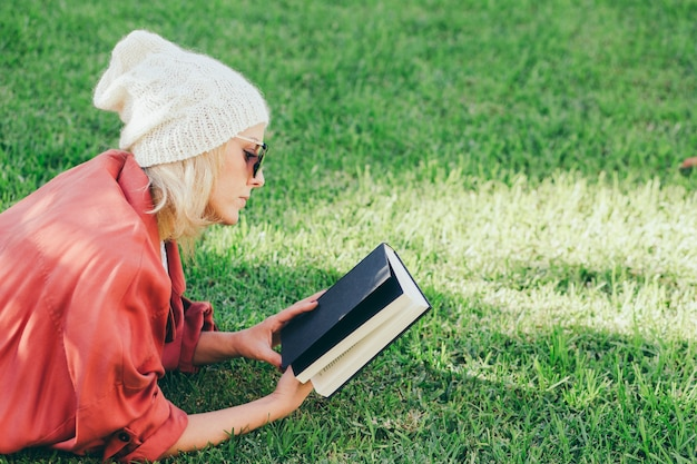 Woman looking at book cover Free Photo