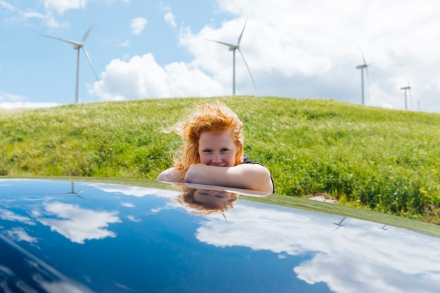 Woman looking at camera getting out of car window and putting hands on roof Free Photo