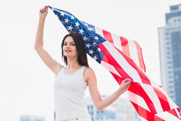 Woman looking at camera and waving american flag Free Photo
