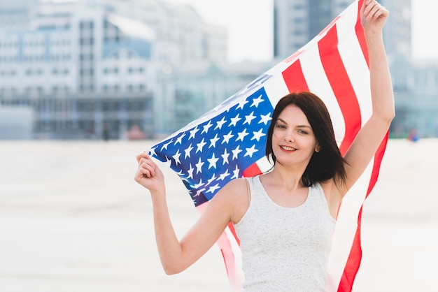 Woman looking at camera and waving wide american flag Free Photo