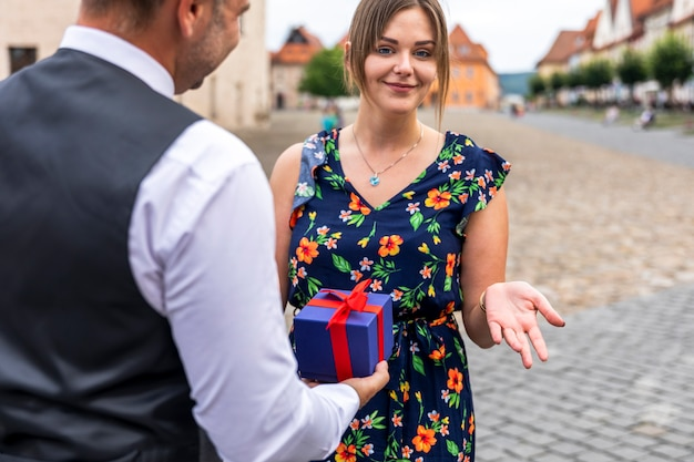 Woman looking at the camera while receiving a gift Free Photo