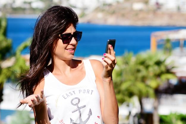 Donna, guardando incredulo tuo cellulare Foto Gratuite