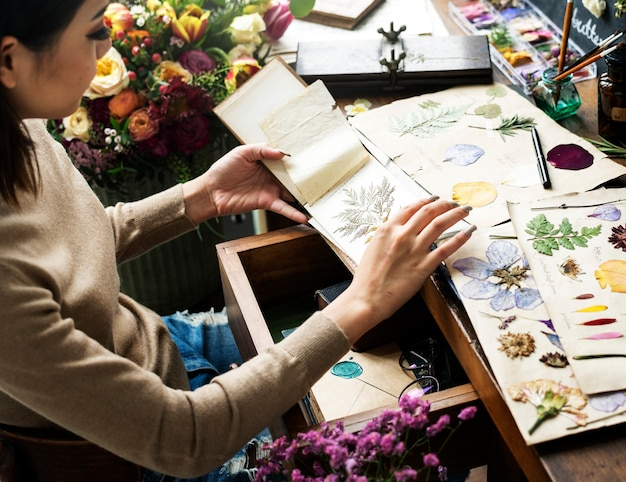 Woman Looking A Dried Flower Book Premium Photo