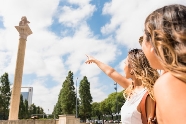 Woman looking at her female friend pointing the finger at pillar in the park Free Photo