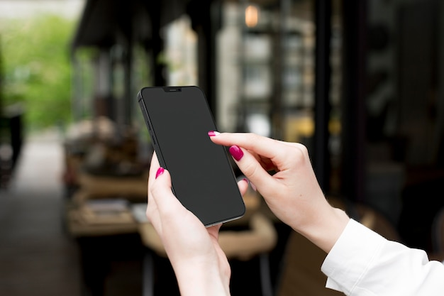 Woman looking at her phone with empty screen Free Photo