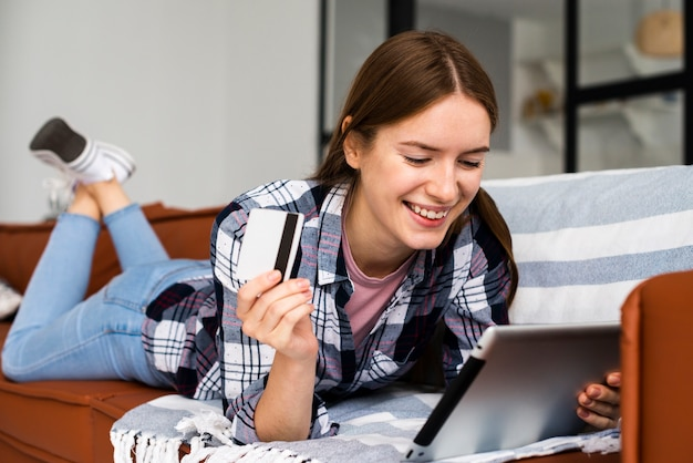 Woman looking at her tablet and holding a credit card Free Photo