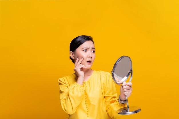 Женщина смотрит в зеркало и переживает морщины на лице Premium Фотографии