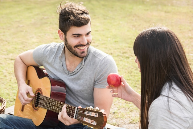 Woman looking at man playing guitar in the park Free Photo