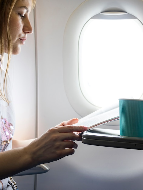 Woman looking at the menu in plane Free Photo