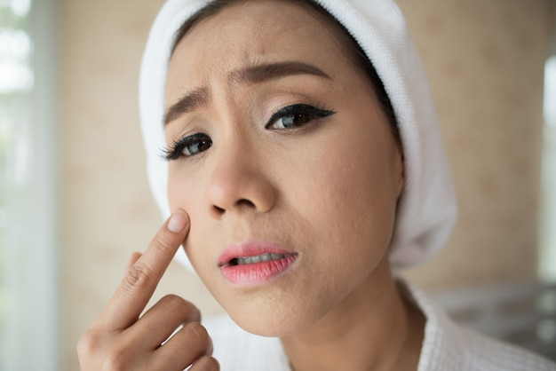 Woman looking at mirror at home and checking her face