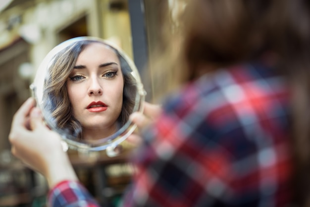 Woman looking in a mirror Free Photo