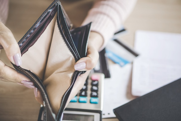 Woman looking for money inside empty wallet Premium Photo