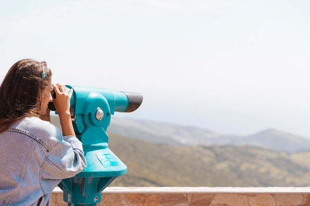 Woman looking at mountains with binoculars Free Photo