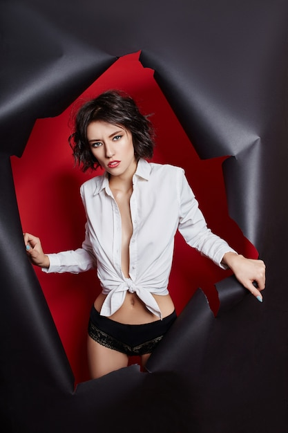Woman looking out of torn paper background. hole Premium Photo