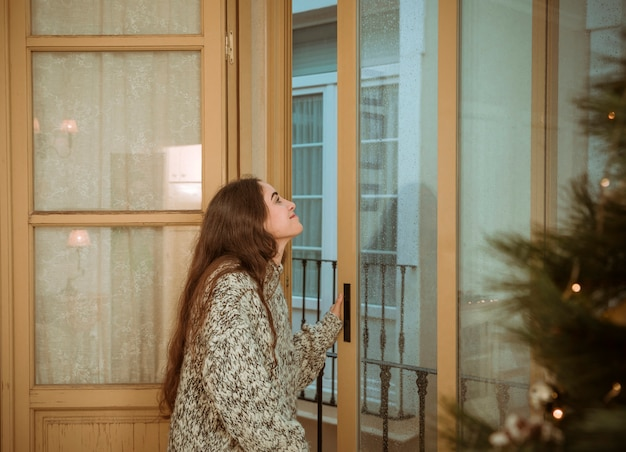 Woman looking out of window next to christmas tree Free Photo