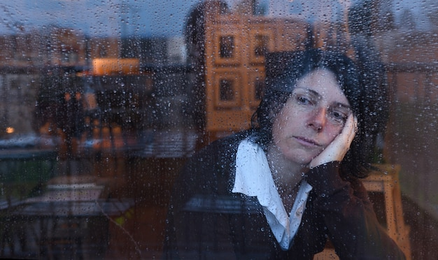 Woman looking out the window on a rainy day Premium Photo