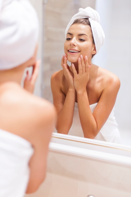 Woman looking on reflection in the mirror after shower Free Photo