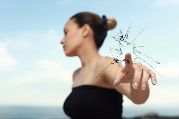 Woman looking to the side while breaking a glass with a finger Free Photo