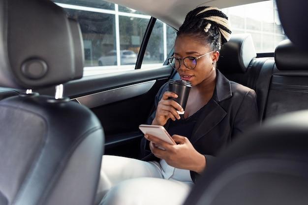 Donna che guarda smartphone e un caffè nella sua auto Foto Gratuite