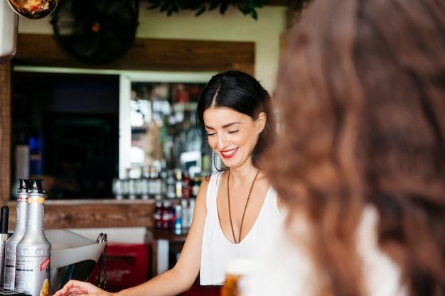 Женщина ищет улыбающегося бармена Бесплатные Фотографии