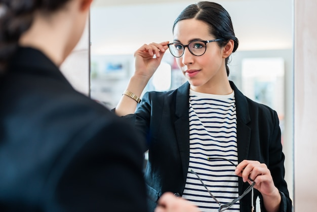 Woman looking with glasses in mirror at optician Premium Photo