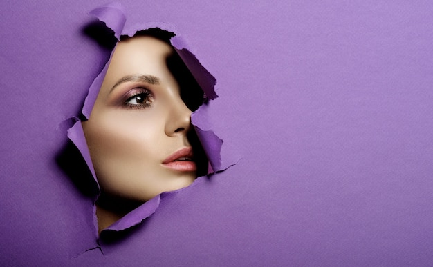 Woman looks in hole colored purple paper, fashion beauty makeup and cosmetics, beauty salon Premium