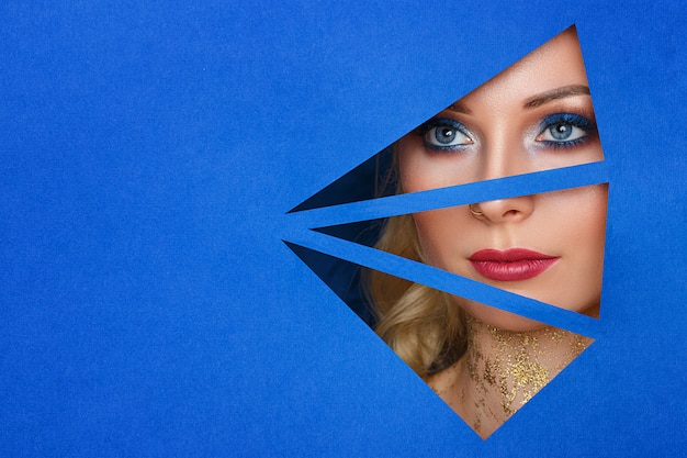 A woman looks in the hole the paper, beautiful make up . Premium Photo