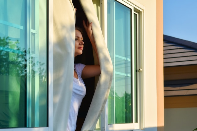 Woman looks out the window in a sunny day. Premium Photo