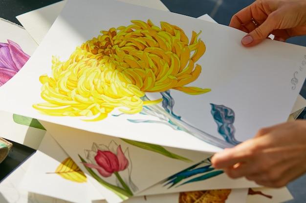 女性は黄色のダリアの花のアクリルイラストを見る 無料写真