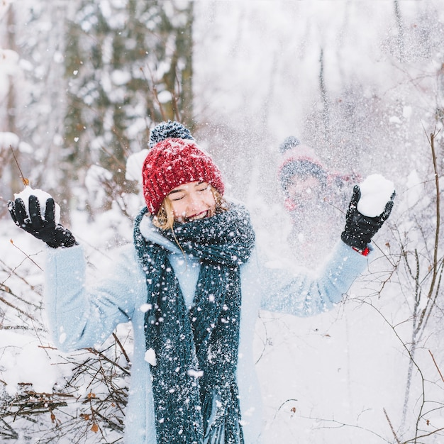 Woman losing snowball game in forest Free Photo
