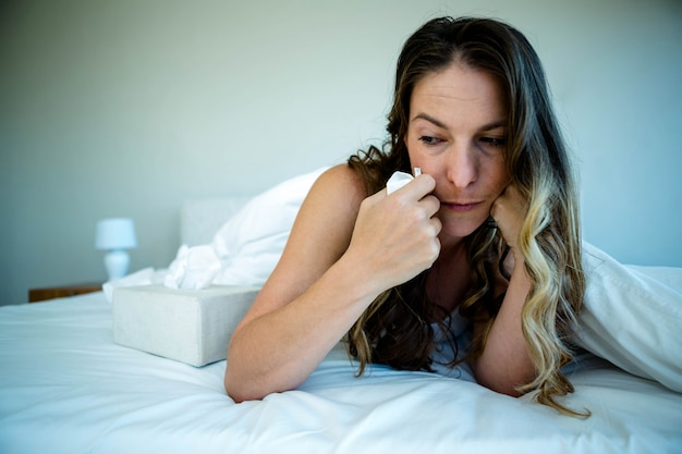 Woman lying in bed looking upset and holding a tissue in her hand Premium Photo