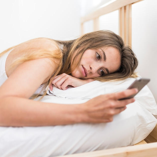 Woman lying on bed using mobile phone Free Photo