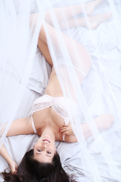 Donna sdraiata sul letto Foto Gratuite