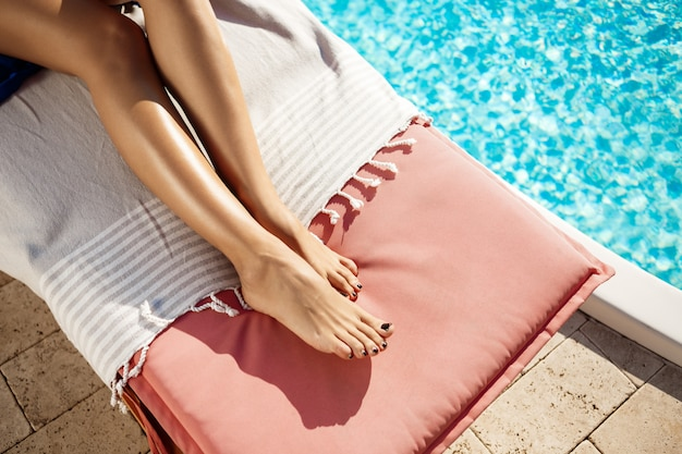 Woman lying on chaise near swimming pool Free Photo