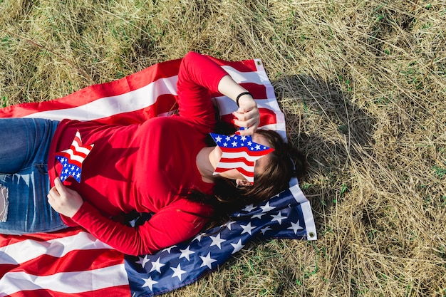Woman lying on fabric of american flag on field Free Photo