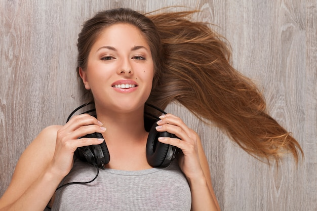 Woman lying on a floor with headphones Free Photo