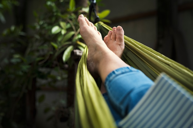 Woman lying on hammock chilling reading book Free Photo