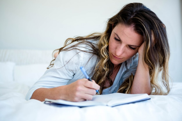 Woman lying in her bed, looking sad and writing in a book Premium Photo
