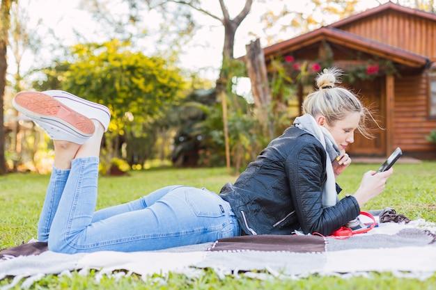 Женщина, лежащая в саду. молодая блондинка женщина со своим мобильным телефоном на открытом воздухе. концепция благополучия и на открытом воздухе. Premium Фотографии