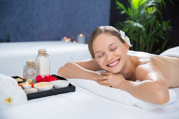 Woman lying in the massage room with a tray of aromas Free Photo