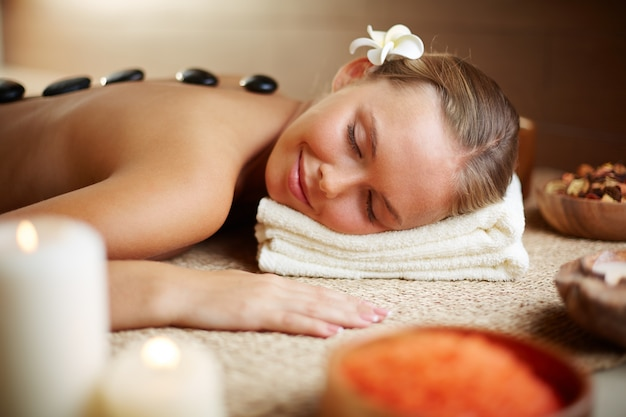 Free Photo | Woman lying on massage table with hot stones