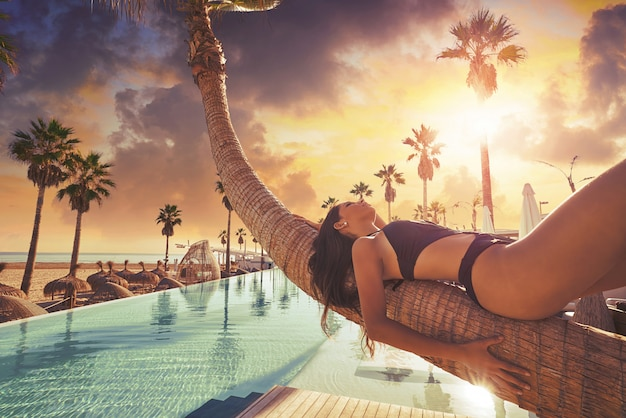 Woman lying on pool bent palm tree trunk Premium Photo