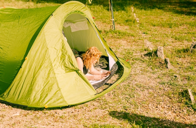 Woman lying in tent with tablet Free Photo