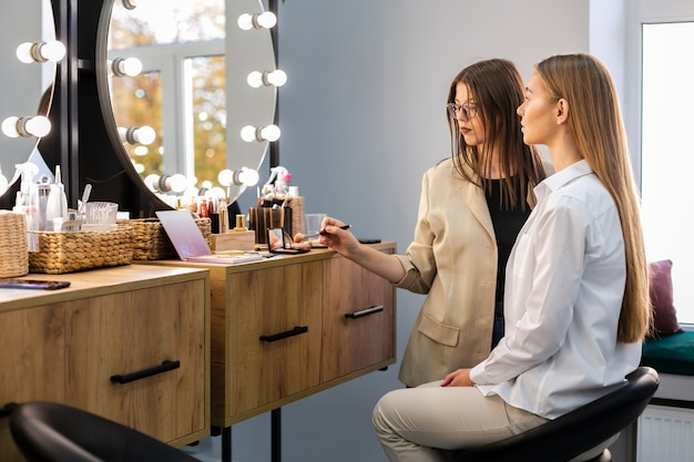 Woman and makeup artist looking at mirror Free Photo