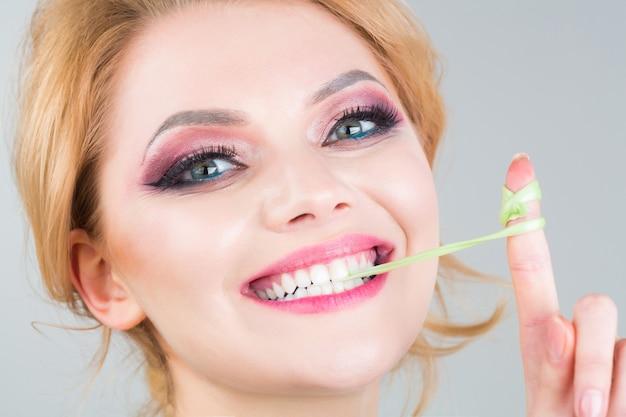女性の化粧、風船ガム、ガム。美しい女性の肖像画。楽しい女性と幸せ。クローズアップの顔、笑顔。 Premium写真